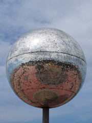 a giant glitter ball on blackpool promenade with blue sky and reflection of the town in the mirrored surface on a sunny day with blue sky