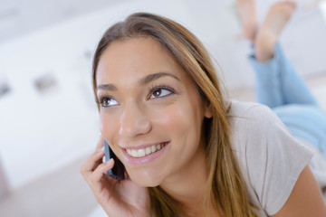 smiling woman using a smartphone while relaxing at home