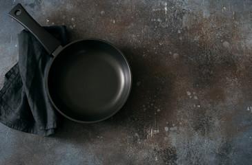 Empty iron pan on dark grunge background