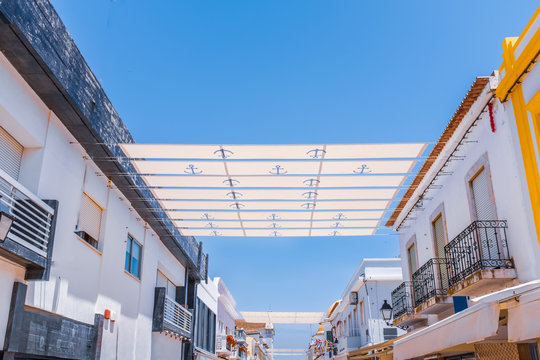 strips of sun shade over a street in portugal attached to roof tops via wires