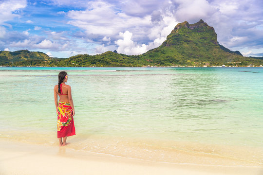 Tahiti luxury travel beach vacation woman walking in polynesian cover-up skirt beachwear on idyllic paradise island in French Polynesia. Red traditional clothes, bikini and flower girl.