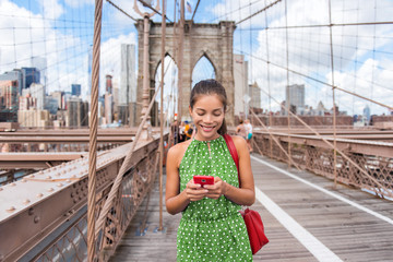 NYC travel phone texting girl holding smartphone on Brooklyn bridge in New York City, Manhattan USA. Asian woman phone reading or using social media in summer.