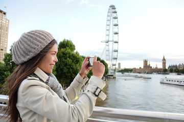 Tourist Asian girl taking picture with phone of London city landscape with popular attraction at Thames River. Europe travel lifestyle. Happy woman holding cellphone outdoors in spring coat.