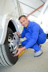 Mechanic fitting hubcap to wheel