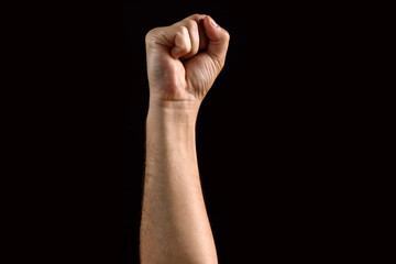 Male fist raised up, isolated on a dark background. Isolate