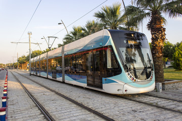 Perspective shot of tramway in movement with pedestrian stones at sunset time in Izmir at Turkey