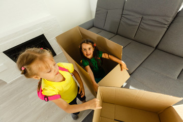 Photo of two girls sitting on sofa among cardboard boxes