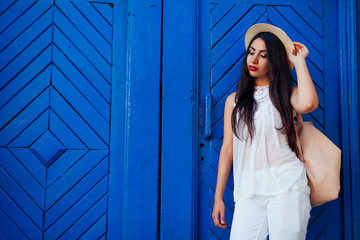 Happy tourist woman smiling against blue wooden door. Outdoor portrait of beautiful college girl wearing summer outfit