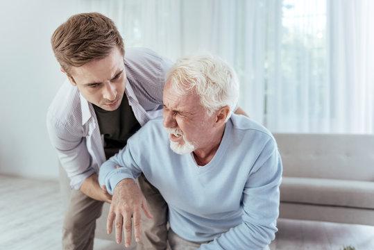 Sudden dizziness. Kind man helping senior man who groaning