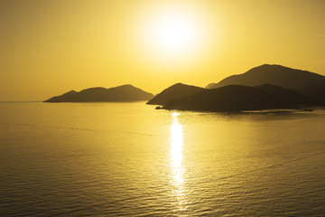 Mediterranean landscape. Sunset on the sea with flowing bright colored rays of the sun through the clouds.  Silhouettes of mountains. Background.