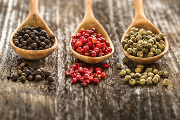 Different pepper in a wooden spoons on wooden table. Fototapete