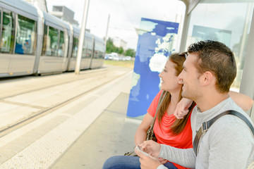 man and woman on a tram stop