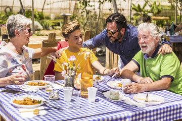 family caucasian people having lunch in natural alternative restaurant all together with joy and fun. smiling and laughing three different generations have nice leisure activity in a day of vacation