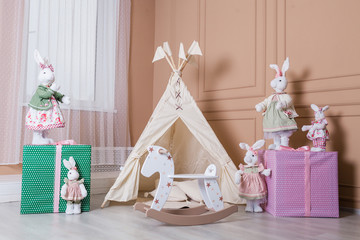 Interior room for a child. Tent for game. Wigwam, toys, rabbits, gifts, rocking horse.