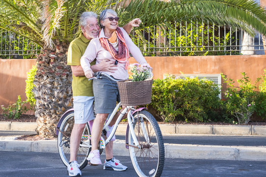 nice caucasian senior adult couple have fun going and moving on a vintage bike together. woman carry a man on an old bicylcle in outdoor leisrue happy activities. nice lifestyle retired people