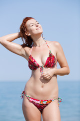 Red haired young woman in bikini drying her hair on beach