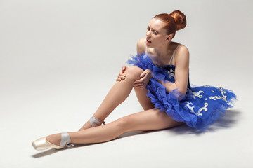 knee pain. ballerina with bun collected hair wearing blue dress and pointe shoes holding on injured knee while sitting on white floor.