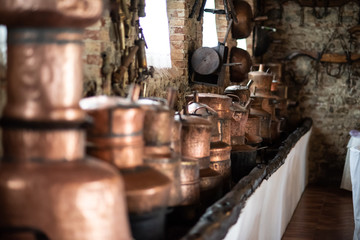 Copper utensils: frying pans, hanging from the ceiling in the kitchen