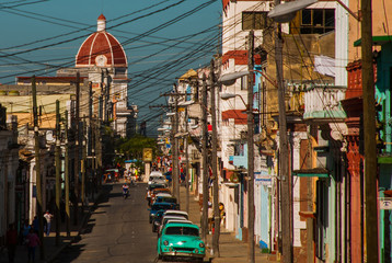 Cienfuegos, Cuba: Street with houses and road with cars, view of the dome of the Municipality.
