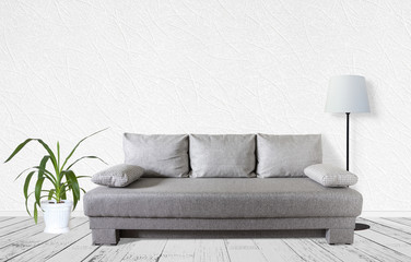 Interior decor mock up. Modern couch with cushions, standard lamp, yucca plant in flower pot near white textured wall
