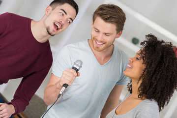 three young people singing into microphone