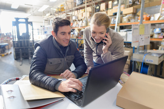 managers working on laptop and talking on phone in warehouse