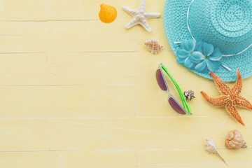 Beach accessories including sunglasses, starfish, hat beach, colorful flip flop and sea shell on bright blue pastel wooden background for summer holiday and vacation concept.