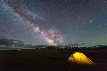 Milky Way on Starry Night Sky with Airglow and Yellow Glowing Tent. Camping Concept