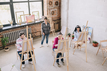 High angle portrait of adult students  painting sitting by easels in art studio with female art teacher watching them in spacious sunlit loft space, copy space