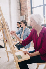 Portrait of art students sitting in row and painting at easels in art studio, focus on smiling  adult  woman enjoying work in center