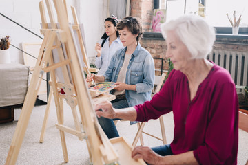 Portrait of art students sitting in row and painting at easels in art studio, focus on smiling  adult  woman enjoying work in center, copy space