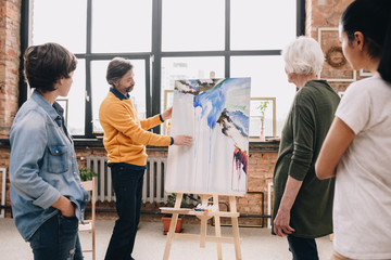 Portrait of mature bearded artist proudly presenting watercolor painting to audience in art studio