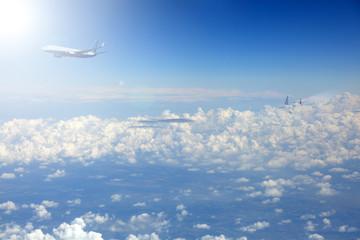 Samolot pasażerski odrzutowy nad chmurami w promieniach słońca.