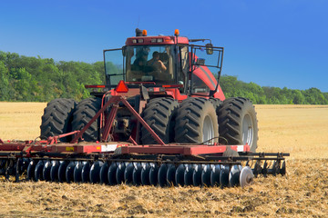 red tractor for harvesting in the midst of the summer season, produces disk field