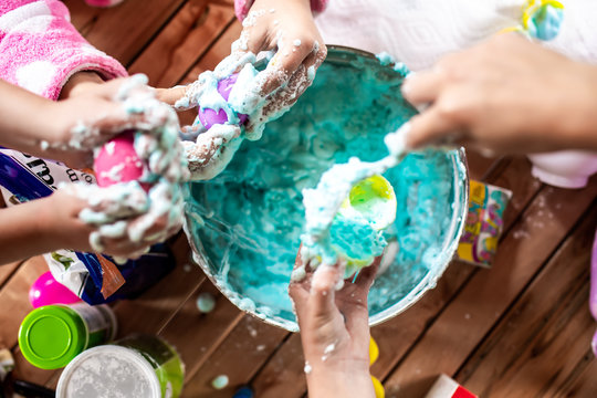A group of young girls, children make a mess with frothy slime at a birthday party