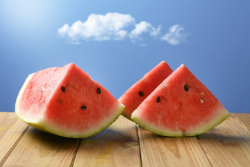 slices of red watermelon on wooden table with blue sky in background
