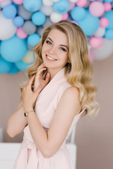 Portrait of a beautiful young girl with curly blonde hair. Stands in a light dress against the background of white and blue balloons. Delicate hair and makeup