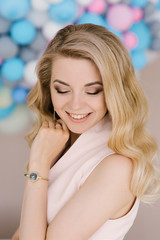 Portrait of a beautiful young girl with curly blonde hair. Stands in a light dress against the background of white and blue balloons. Eyes look down with beautiful makeup closeup