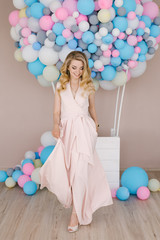 Portrait of a beautiful young girl with curly blonde hair in full growth. Standing and dancing in a light dress against the background of white and blue balloons.
