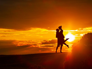 Romantic couple on countryside at the sunset with the sun and one tree