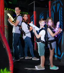 Kids standing back to back with laser pistols