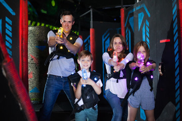 Parents and children playing laser tag