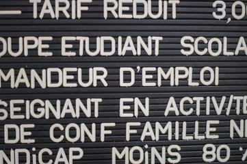 Tableau noir avec tarifs pour différentes catégories de consommateurs, en français