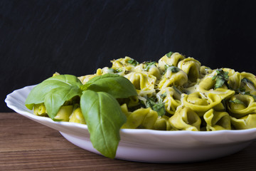 italian pasta dish prepared with cheese, vegetables and basil leaf