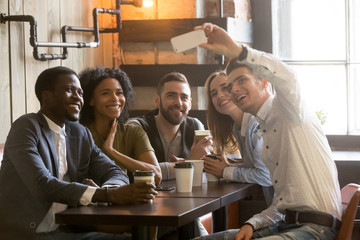 Smiling Caucasian man taking self-portrait on smartphone with multiracial friends sitting in coffee shop, diverse people shooting, making selfie on phone camera, chilling having fun out in cafe
