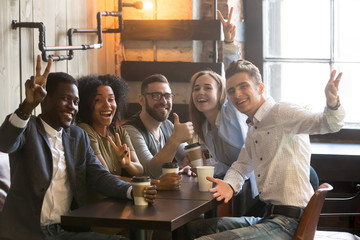 Portrait of smiling multiracial friends having fun together, drinking coffee in cafe, happy millennials posing to camera enjoying meeting in cafe, excited colleagues looking at camera chilling out
