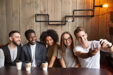 Young Caucasian man making self-portrait on smartphone during casual meeting with multiracial friends in loft coffeeshop, diverse colleagues smiling posing for group photo while having coffee in cafe