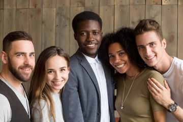 Portrait of happy multiracial people smiling at camera showing racial unity and equality, diverse millennial students being united posing for picture, laughing and having good time together.