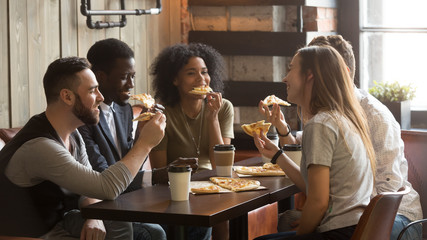 Smiling multiracial friends eating pizza and drinking coffee, laughing and having fun in restaurant, diverse millennial colleagues enjoying lunch during work break sitting at coffee table in loft cafe