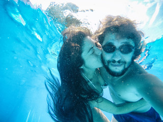 happy couple under the water in a pool